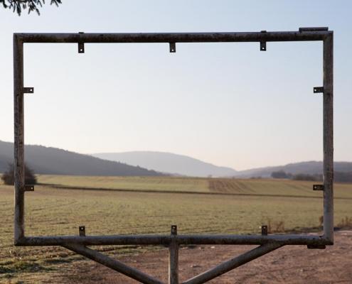 Blick durch einen Rahmen auf die weite einer Landschaft